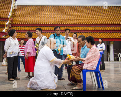Bangkok, Thailand. 21st July, 2013. A young man entering the monastery for Vassa makes an offering to his parents - Stock Photo