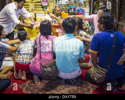 Bangkok, Thailand. 21st July, 2013. A family makes merit and presents a senior monk with alms at Wat Mahabut on - Stock Photo
