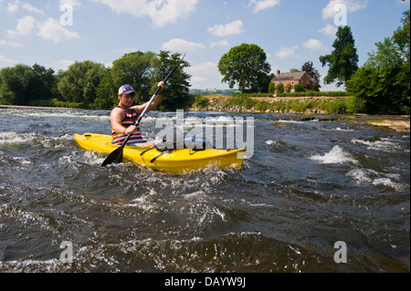 Canoeist in kayak type yellow canoe paddling down the River Wye at Hay on Wye Powys Wales UK - Stock Photo
