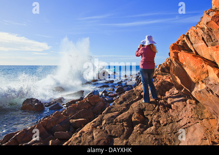 pretty woman taking a photo of waves breaking over the rocks rocky coast at Hallett Cove Adelaide South Australia - Stock Photo
