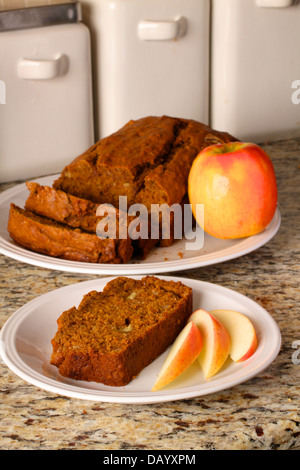 A slice of homemade banana nut bread is plated in front of a partially sliced loaf of bread, along with fresh apple - Stock Photo