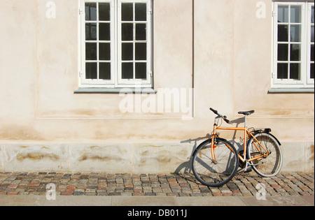A bike is left outside a building on a side street of Strøget in Copenhagen, Denmark - Stock Photo