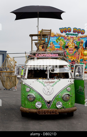 Volkswagen Camper Van/Bus Hippy bus with Table chairs and a Umbrella on the roof - Stock Photo
