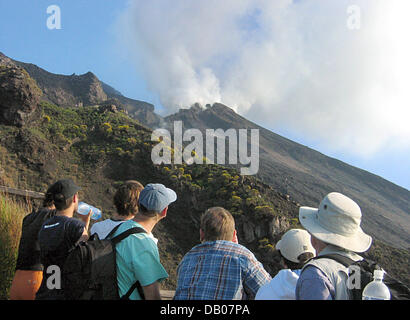 Tourists watch the plume of the active volcano Stromboli on the Aeolian island of the same name in Italy, 30 May - Stock Photo