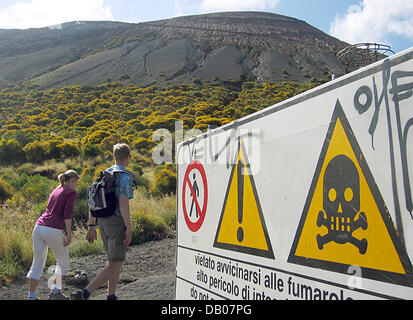 Tourists pass a sign cautioning against the toxic sulfur fumaroles escaping from the volcano Gran Cratere on the - Stock Photo