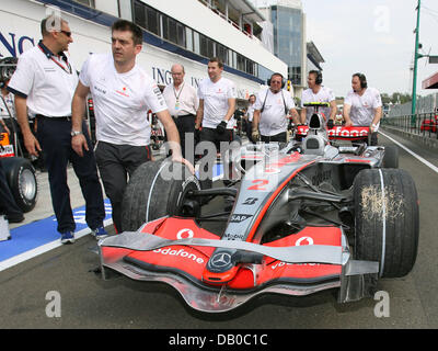The race car of British Formula One rookie Lewis Hamilton of McLaren Mercedes is pushed back into the pits after - Stock Photo