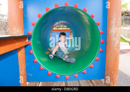 Young Child playing in a green play tunnel in playground - Stock Photo