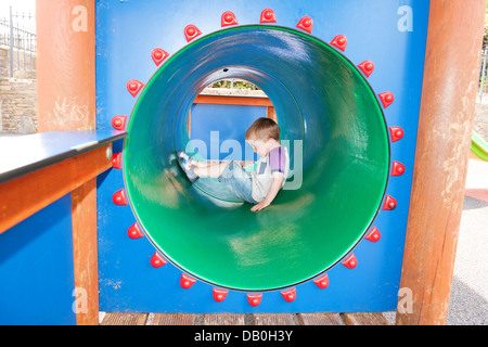 Young Child playing inside a green play tunnel in playground - Stock Photo
