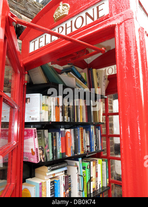 Interior of an old red British Telephone box turned into a British village eccentric lending library - Stock Photo