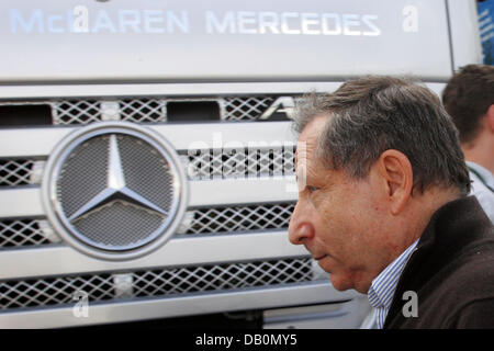 French Jean Todt, CEO of Scuderia Ferrari, walks past a truck of McLaren Mercedes after the second practice session - Stock Photo