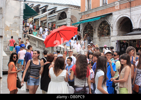 Happy young people on a guided tour in Venice (in front of Rialto Bridge). - Stock Photo