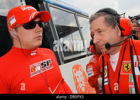 Finnish Formula One driver Kimi Raikkonen of Scuderia Ferrari (L) speaks with French Jean Todt, CEO of Scuderia - Stock Photo