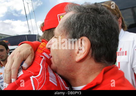 Finnish Formula One driver Kimi Raikkonen of Scuderia Ferrari (L) receives congratulation from French Jean Todt, - Stock Photo