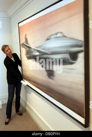 An employee of the auction house Christie's holds the Gerhard Richters painting ' Jet Fighter' in Duesseldorf, Germany, - Stock Photo