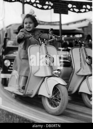 festivities, public festival, young girl on motor scooter on childrens' carousel, 1950s, Additional-Rights-Clearences - Stock Photo