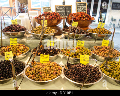 Olives and sun dried tomatoes on sale in the covered market in Antibes, France - Stock Photo
