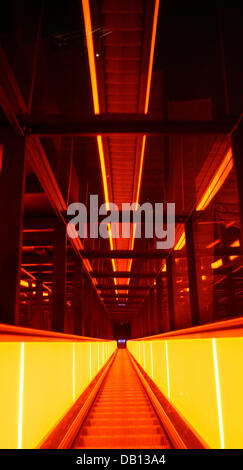 View into the very steep and long escalator illuminated in screaming orange light at the former colliery Zollverein - Stock Photo
