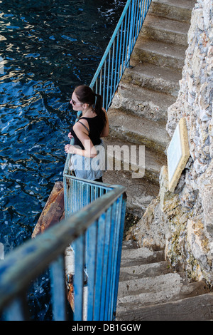 Brunette Woman Standing At A Blue Railing Next To The Sea - Stock Photo