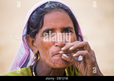 Rural Indian woman smoking near Delhi, India - Stock Photo