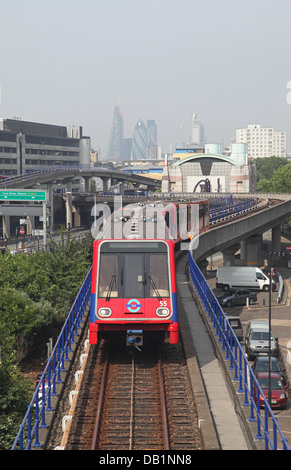 A London Docklands Light Railway train approaches Poplar station with the City of London in the background - Stock Photo