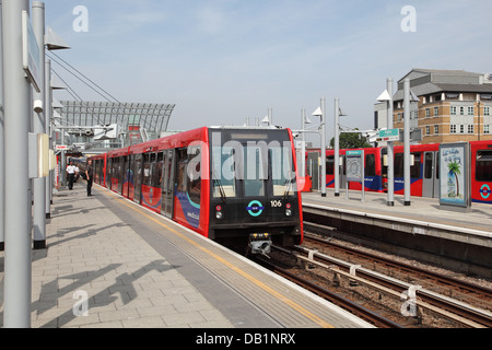 A London Docklands Light Railway train departs from Poplar Station - Stock Photo