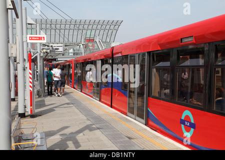 A London Docklands Light Railway train arrives at Poplar Station - Stock Photo