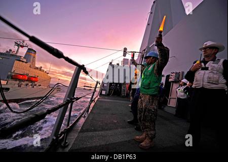 Boatswain's Mate 2nd Class Cory Shields signals to the Military Sealift Command fleet replenishment oiler USNS Henry - Stock Photo