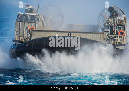 A landing craft air cushion (LCAC), piloted by Sailors assigned to Naval Beach Unit (NBU) 7, makes its approach - Stock Photo