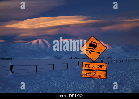 Icy road warning sign and alpenglow on Hawkdun Range, and lenticular clouds, Maniototo, Central Otago, South Island, - Stock Photo