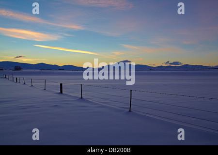 Sunset over snowy farmland near Oturehua, Maniototo, Central Otago, South Island, New Zealand - Stock Photo