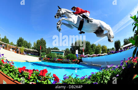 German equestrian Marco Kutscher jumps over a hurdle on his horse Cornet Obolensky during the European Show Jumping - Stock Photo