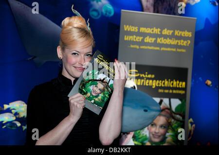 Moderator and writer Enie van de Meiklokjes poses with her first book 'Enies Aquariengeschichten' at Sea Life aquarium - Stock Photo