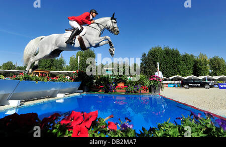 German show jumper Marco Kutscher jumps a water obstacle on his horse Cornet Obolensky at the European Show Jumping - Stock Photo