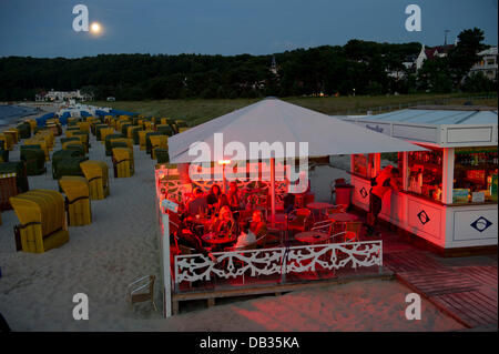 The full moon shines over the beach in Binz on Ruegen, Germany, 22 July 2013. Tourists sit in a beach bar and enjoy - Stock Photo
