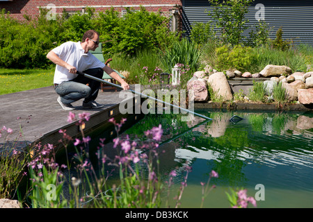 man kneeling on a wooden terrace and fishing with a net in the pond - Stock Photo