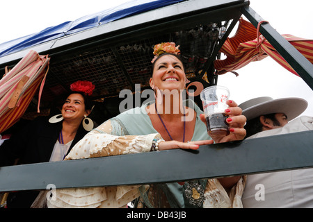 Women wearing Spanish Flamenco dresses in gypsy horse-drawn carriages on the pilgrimage route to El Rocio in Spain - Stock Photo