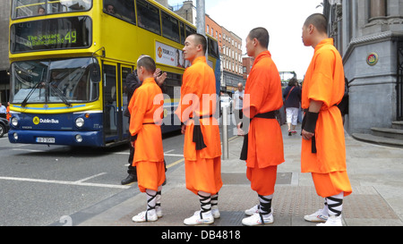 Shaolin Warriors wait at traffic lights on Dame Street after a press call during the build up to shows at the Olympia - Stock Photo