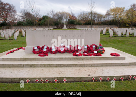 Rows of war graves & circular red poppy wreaths on Stone of Remembrance after ceremony - Stonefall Cemetery, Harrogate, - Stock Photo