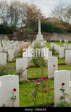 Rows of white inscribed headstones on war graves (with red rose) & Cross of Sacrifice beyond - Stonefall Cemetery, - Stock Photo