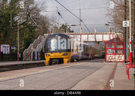 Northern Rail train (engine cab & coaches) pulling up to deserted station platform on sunny day - Burley in Wharfedale, - Stock Photo