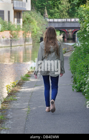 rear view of young woman walking alone along canal towpath, Leicester, England, UK - Stock Photo