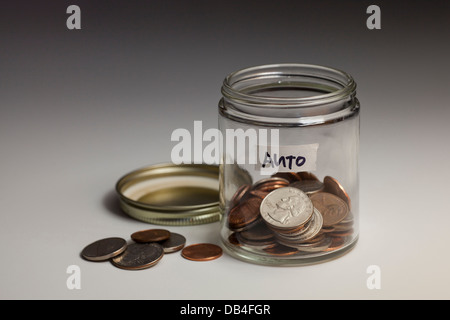 Coins in glass jar saved for car - USA - Stock Photo