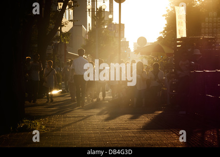 Visitors to the Akita Kanto Festival arriving at Akita City in the evening - Stock Photo