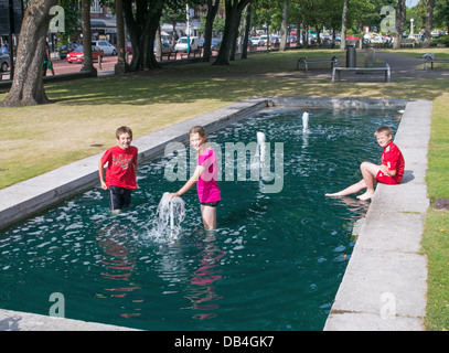 Children cool off in water feature in Southport park during summer heatwave, north west England, UK - Stock Photo