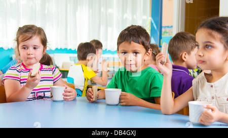 Cute little children drinking milk at daycare - Stock Photo