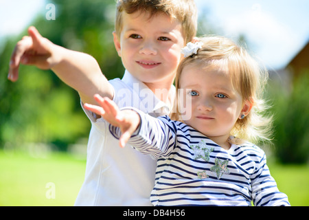 Little brother and sisiter playing in garden - Stock Photo