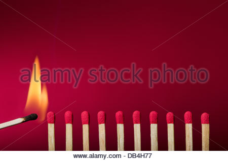 Burning match setting fire to its neighbors, a metaphor for ideas and inspiration - Stock Photo