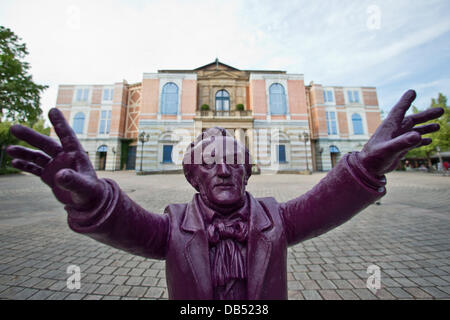 A statue of composer Richard Wagner by artist Ottmar Hoerl is visible in front of the Bayreuth Festival Theatre - Stock Photo