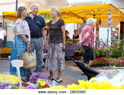 Senior friends shopping in a market - Stock Photo