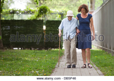 Daughter walking with her mother in a garden - Stock Photo